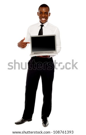 Cheerful male executive pointing at open laptop, full length portrait
