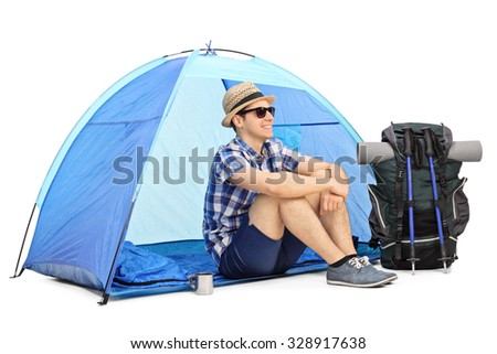 Cheerful male hiker sitting on the floor in front of a blue tent with his backpack and hiking equipment beside him isolated on white background - stock photo