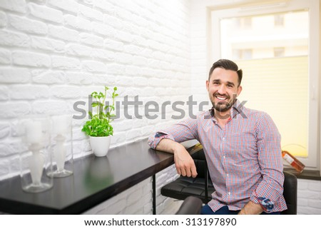 Cheerful male in casual wear sitting in kitchen and smiling - stock photo