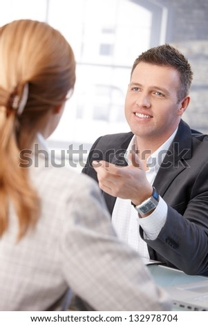 Cheerful male manager interviewing female candidate in office. - stock photo
