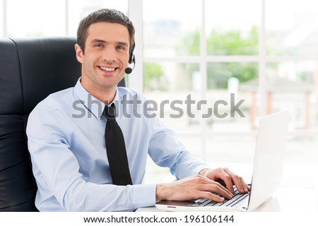 Cheerful male operator. Side view of cheerful young man in headset looking at camera and smiling while using laptop - stock photo
