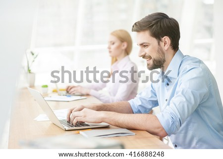 Cheerful male student is working on computer - stock photo