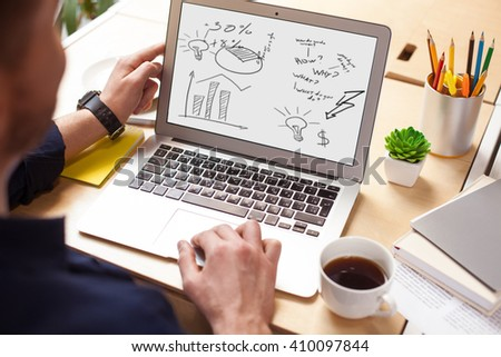 Cheerful male student is working with computer - stock photo