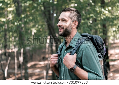 Cheerful male tourist hiking in the woods