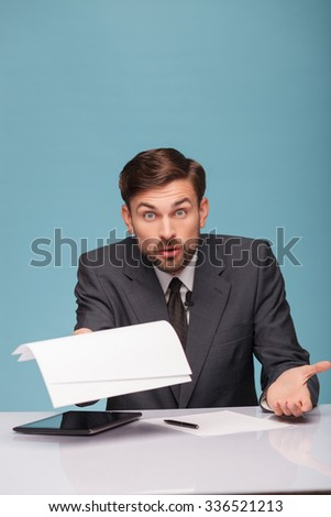 Cheerful male tv reporter is looking at camera with shock. He is holding papers and raising in with question. The man is sitting at a desk near the tablet. Isolated on blue background
