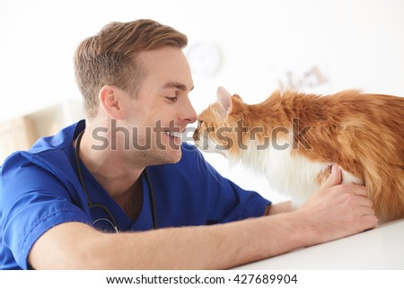 Cheerful male veterinarian is doing checkup of animal - stock photo