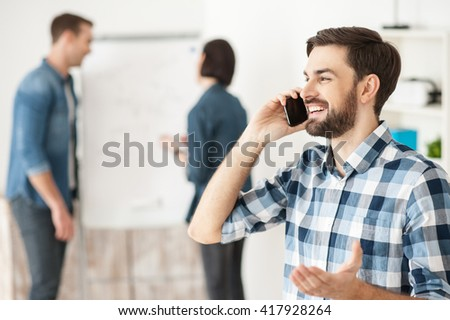 Cheerful male worker is communication on telephone - stock photo