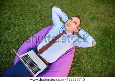 Cheerful male worker resting in park - stock photo