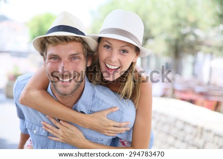 Cheerful man giving piggyback ride to girlfriend - stock photo