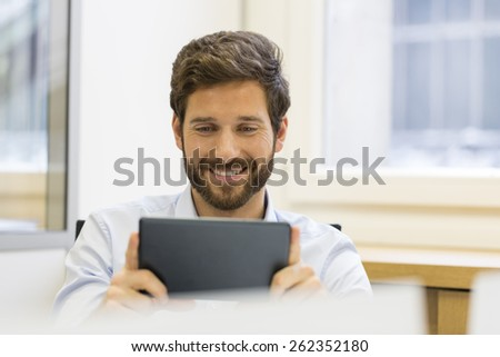 Cheerful man holding tablet pc in office - stock photo