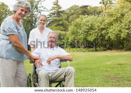 Cheerful man in a wheelchair with his nurse and wife smiling at camera in the park