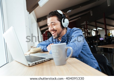 Cheerful man in headset using laptop computer in office - stock photo