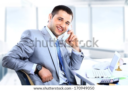 Cheerful man in office answering the phone - stock photo