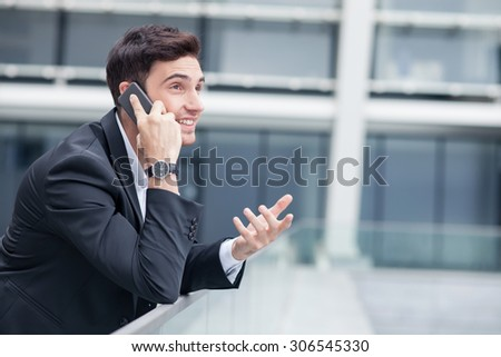 Cheerful man in suit is talking on the phone with his business partner. He is explaining his ideas with aspirations and smiling. The man is leaning on the border near office. Copy space in right side - stock photo