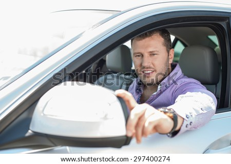 Cheerful man is adjusting side mirror of his car and looking at it with concentration. He is sitting at steering wheel and smiling - stock photo