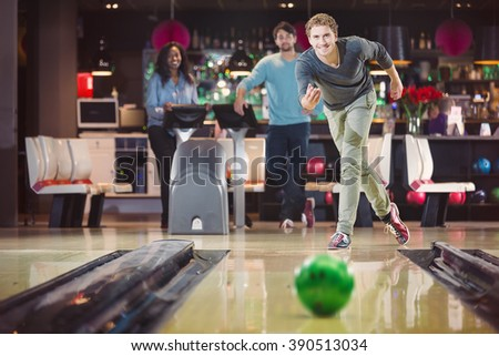 Cheerful man is bowling with his coworkers for the team spirit