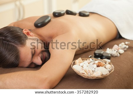Cheerful man is lying at spa and relaxing. The hot stones on his back are massaging him. The man is smiling. His eyes are closed with pleasure - stock photo