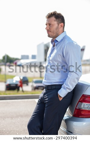 Cheerful man is waiting for his business partner in the airport. He is leaning on his car and looking forward with attention