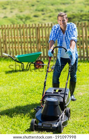 cheerful man lawn mowing in his home garden - stock photo