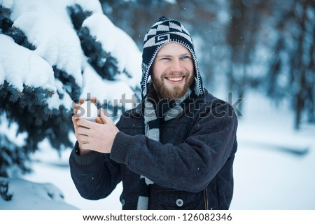 Cheerful man playing in the snow