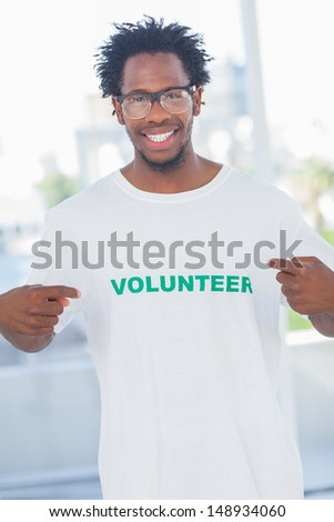 Cheerful man pointing to his volunteer tshirt in a modern office - stock photo