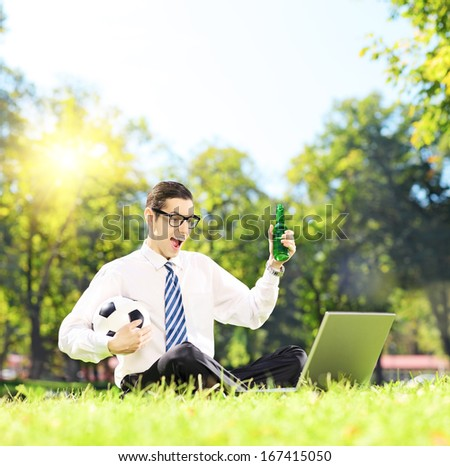 Cheerful man seated on a green grass watching football on a laptop in a park, shot with a tilt and shift lens - stock photo