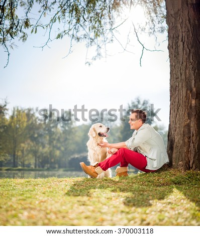 Cheerful man sitting by a tree in park and playing with his pet dog shot with tilt and shift lens  - stock photo