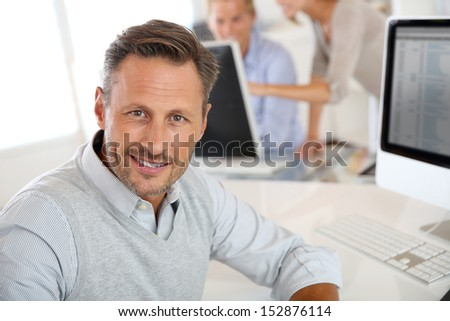 Cheerful man sitting in office and working on desktop - stock photo