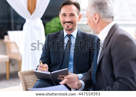 Cheerful man sitting on the couch with his colleague