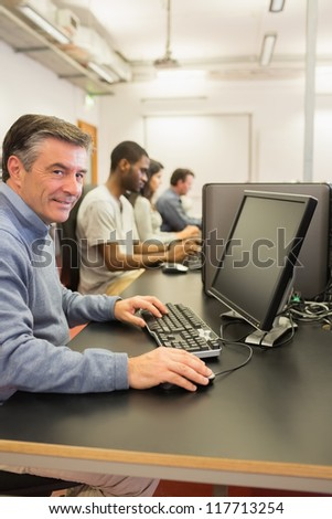 Cheerful man using the computer while working in a class