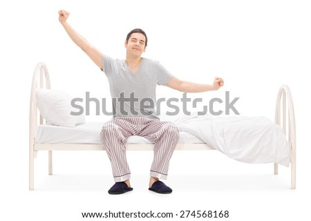 Cheerful man waking up from sleep and stretching seated on his bed isolated on white background