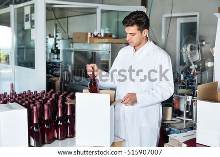 Cheerful man winery worker in uniform packing wine bottles on a winery factory
