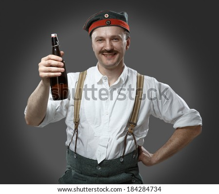 Cheerful man with a beer bottle. Concept - oktoberfest. - stock photo