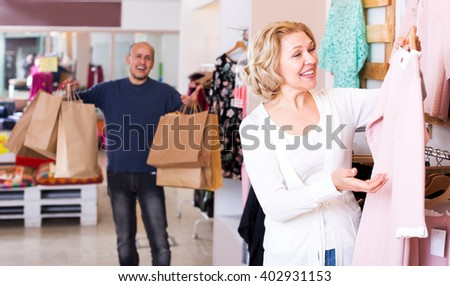 Cheerful man with bags waiting for mature woman selecting dress in boutique
