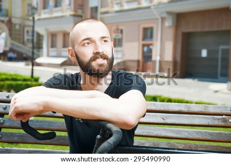 Cheerful man with beard is dreaming and looking aside with smile . He is sitting on bench and leaning on bicycle - stock photo