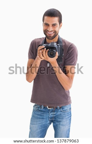Cheerful man with camera around his neck on white background