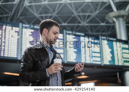 Cheerful man with coffee on the mobile phone in front of Board schedules in airport terminal - stock photo