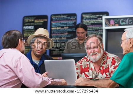 Cheerful man with diverse friends in cafe - stock photo