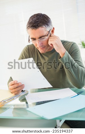 Cheerful man with glasses reading paper in his office