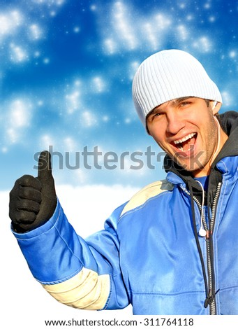 Cheerful Man with Thumb Up on the Winter Background - stock photo