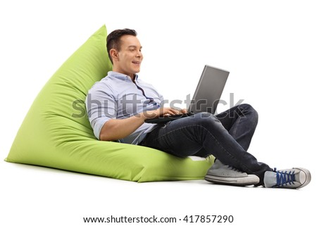 Cheerful man working on laptop seated on a green beanbag isolated on white background - stock photo