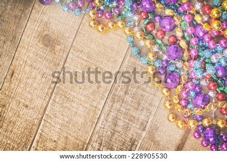 Cheerful Mardi Gras Beads in corner on Rustic Wood Board Background from above with room or space for copy, text, your words.  Horizontal, faded vintage.   - stock photo