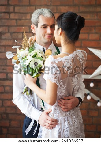 Cheerful married couple dancing near the brick wall decorated with the stars
