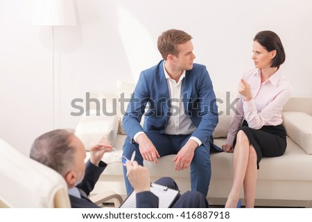 Cheerful married couple is consulting in psychologist - stock photo
