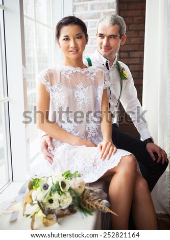 Cheerful married couple sitting near the window - stock photo