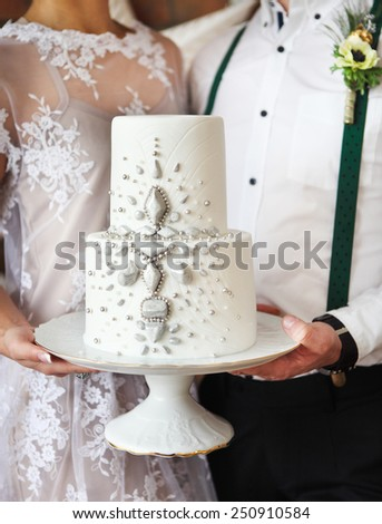 Cheerful married couple standing near the brick wall. Focus on cake - stock photo