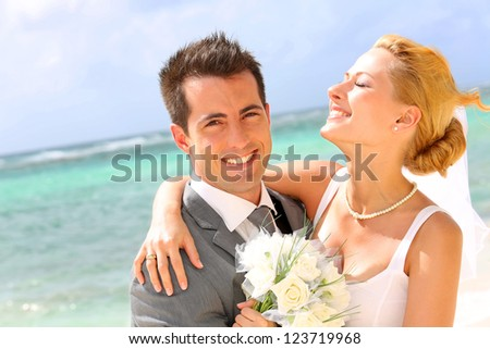 Cheerful married couple standing on the beach - stock photo