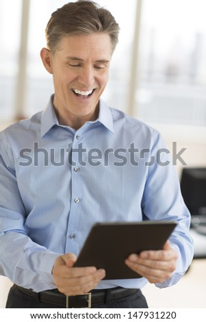Cheerful mature businessman using digital tablet in office - stock photo