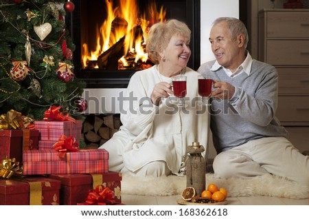 Cheerful mature couple celebrating Christmas holidays  in front of fireplace  - stock photo