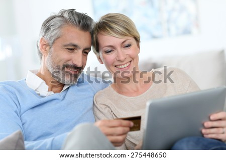 Cheerful mature couple e-shopping on internet - stock photo